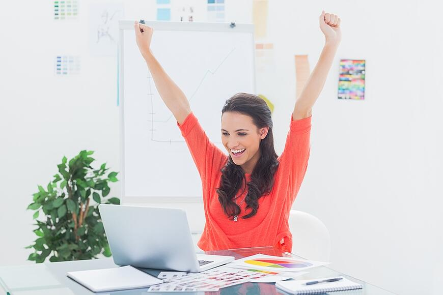 Excited woman raising her arms while working on her laptop in her office.jpeg